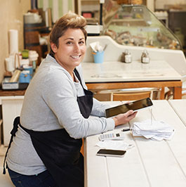 woman behind a counter at a restaurant smiling at the camera and using a tablet