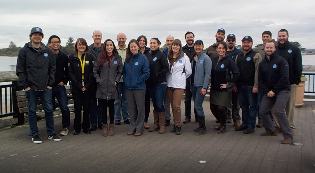 A group of 20 RCEA staff standing on the Eureka waterfont with a cloudy gray sky behind them