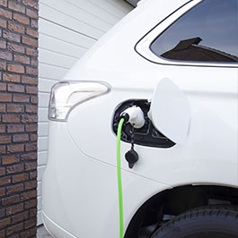 White electric vehicle with charging cord connected