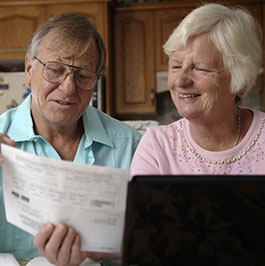 older man and woman looking at their bill