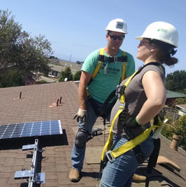 workers on a roof installing solar panels