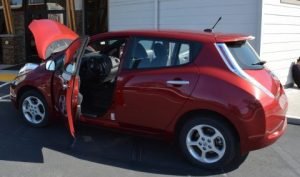 Red battery electric vehicle with driver door and car hood open