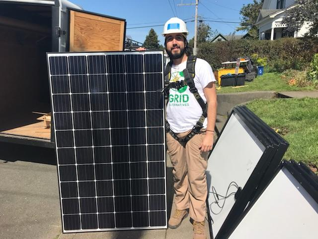 worker holding up solar panel
