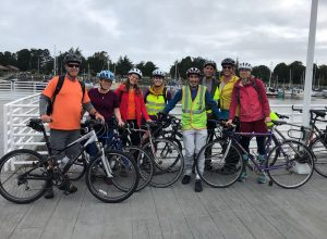 Eight RCEA staff with their bikes and helmets on standing in front of the Eureka waterfront