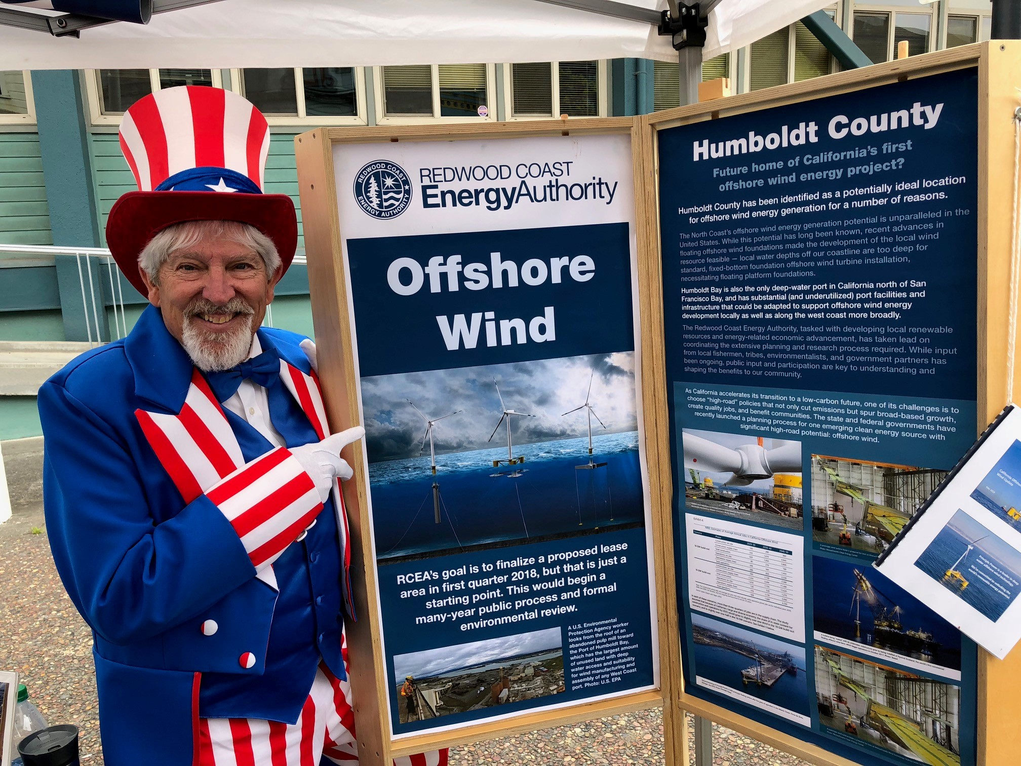 Man dressed in American garb next to an RCEA poster for offshore wind project