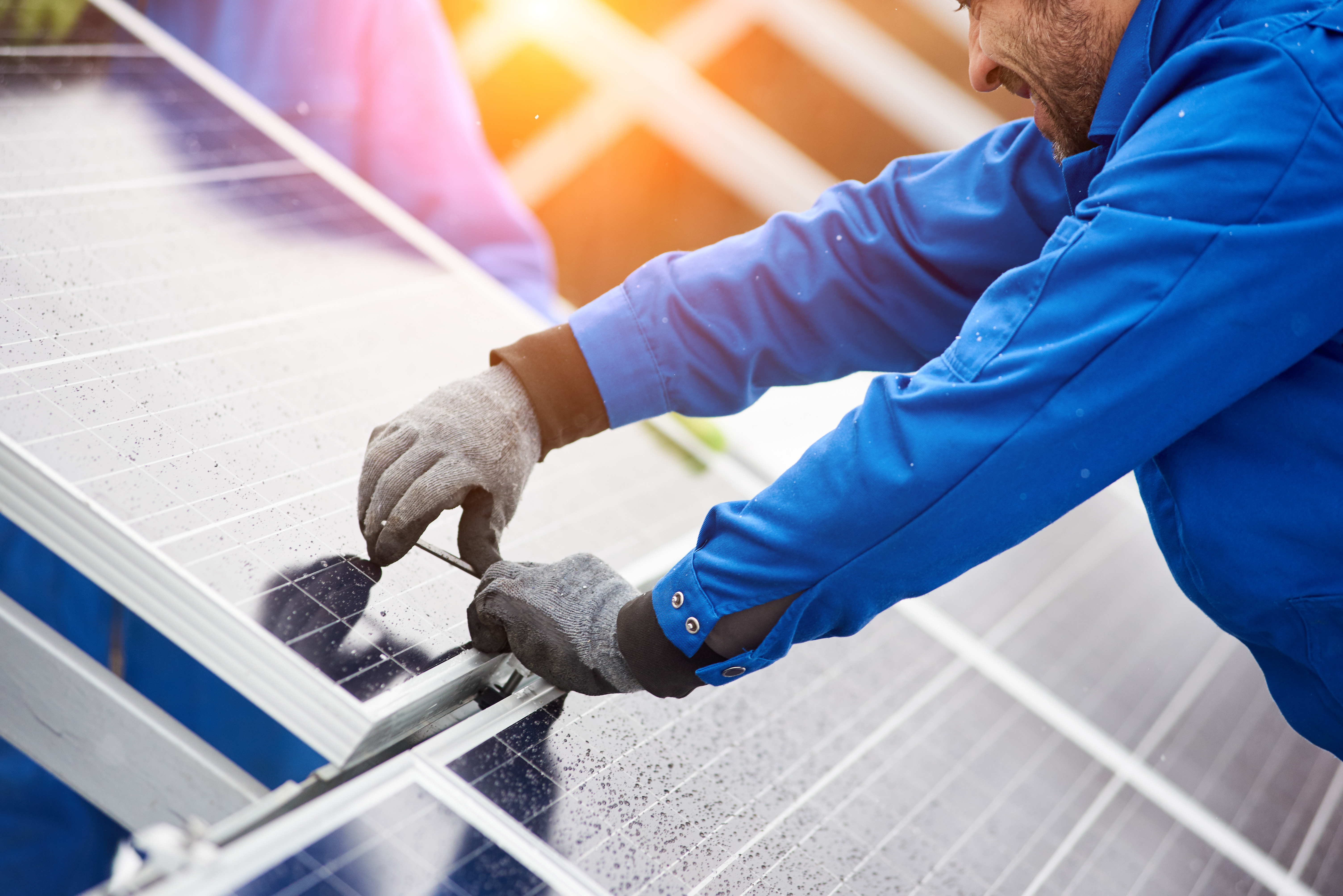 Smiling male technician in blue suit installing photovoltaic blue solar modules with screw