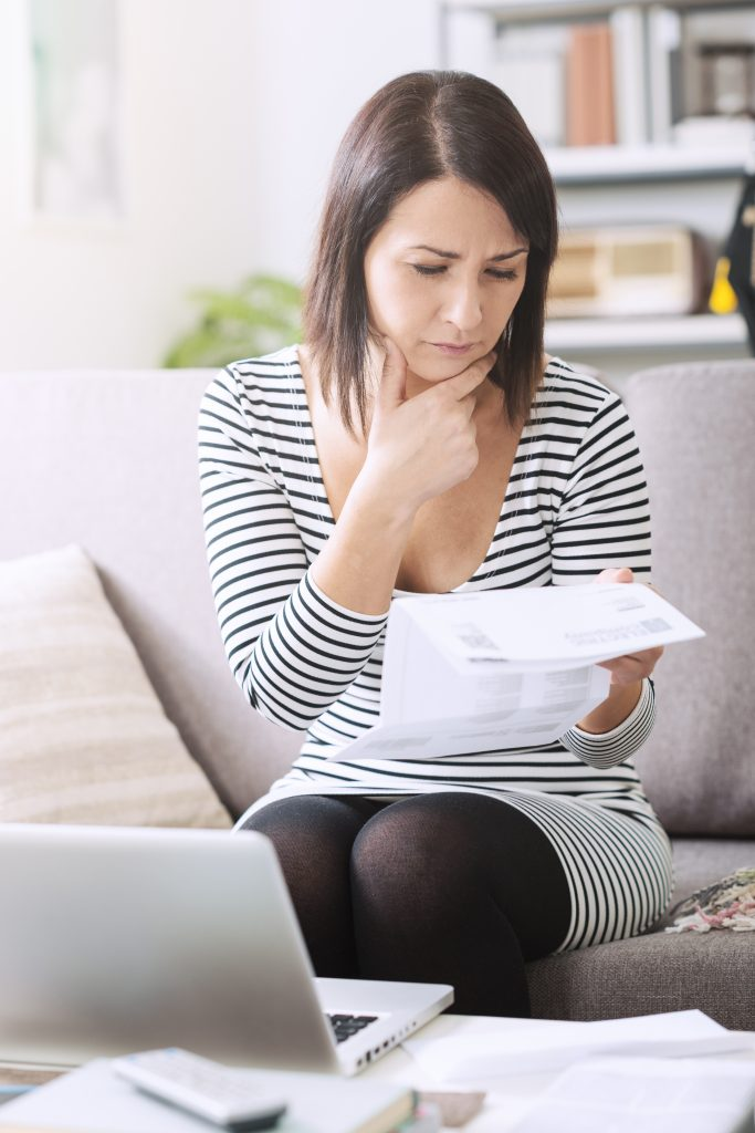 Woman at home sitting on the sofa and checking her electricity bill, she is pensive and thinking with hand on chin