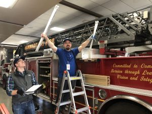 Two RCEA staff in a fire station. one holds two lightbulbs in his hand and is smiling while the other watches while holding a clipboard