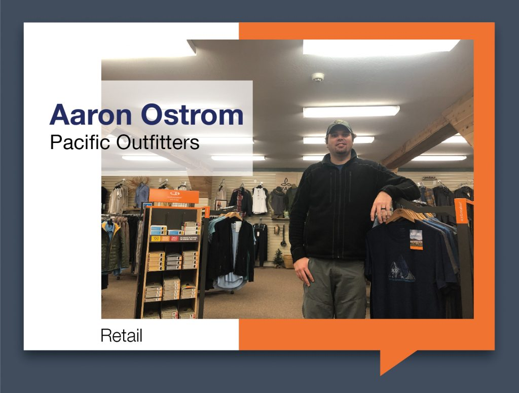 Aaron Ostrom standing next ti a rack of shirts in Pacific Outfitters