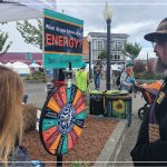 "Two people in the Arcata plaza at the North Country Fair, standing in front of a spinner wheel that says ""What do you know about energy?"""