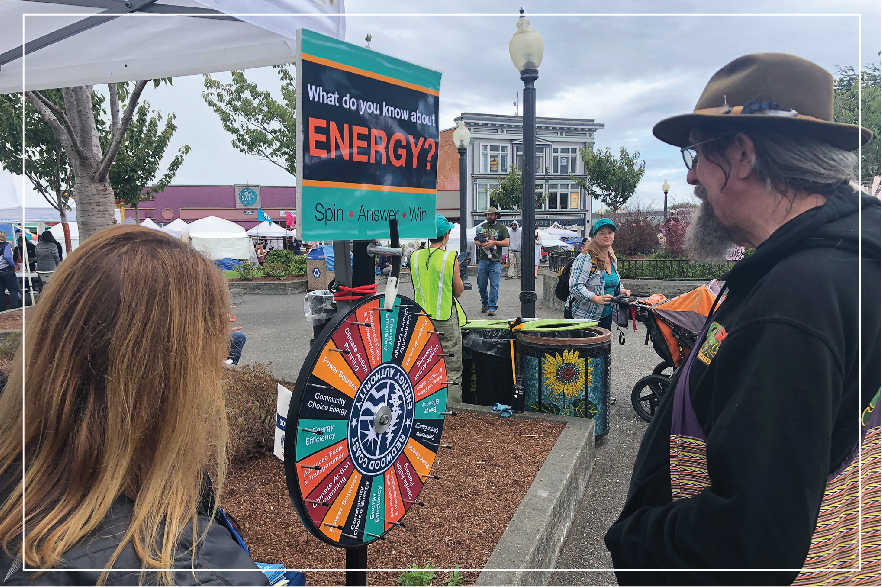"""Two people in the Arcata plaza, standing in front of a spinner wheel that says """"What do you know about energy?"""""""