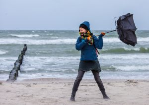 Person holding an umbrella being blown backwards next to a windy ocean
