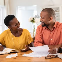 Cheerful mature couple sitting and managing expenses at home