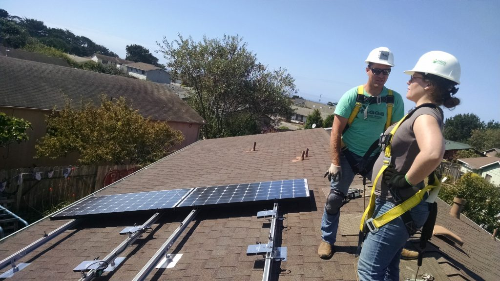 Two solar installers on a roof talking to each other
