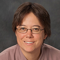 Karen Douglas, woman with straight brown hair and oval glasses in pink shirt