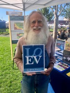 older man with long white beard holding a LOEV sign