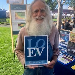 older white man with long white beard holding a LOEV sign
