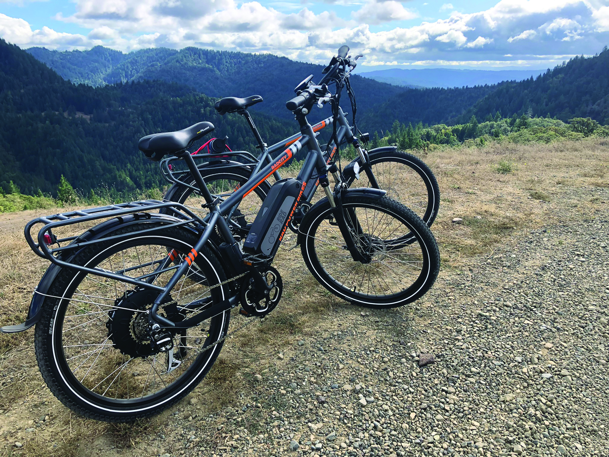 Two electric bikes parked on the side of the road in Kneeland overlooking the mountain side
