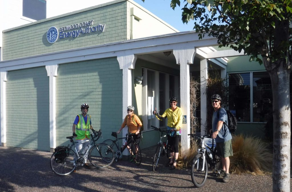 four smiling people wearing biking gear and standing in front of Redwood Coast Energy Authority building with their bikes