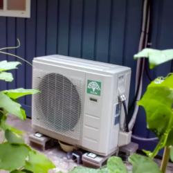 Heat pump in garden by house