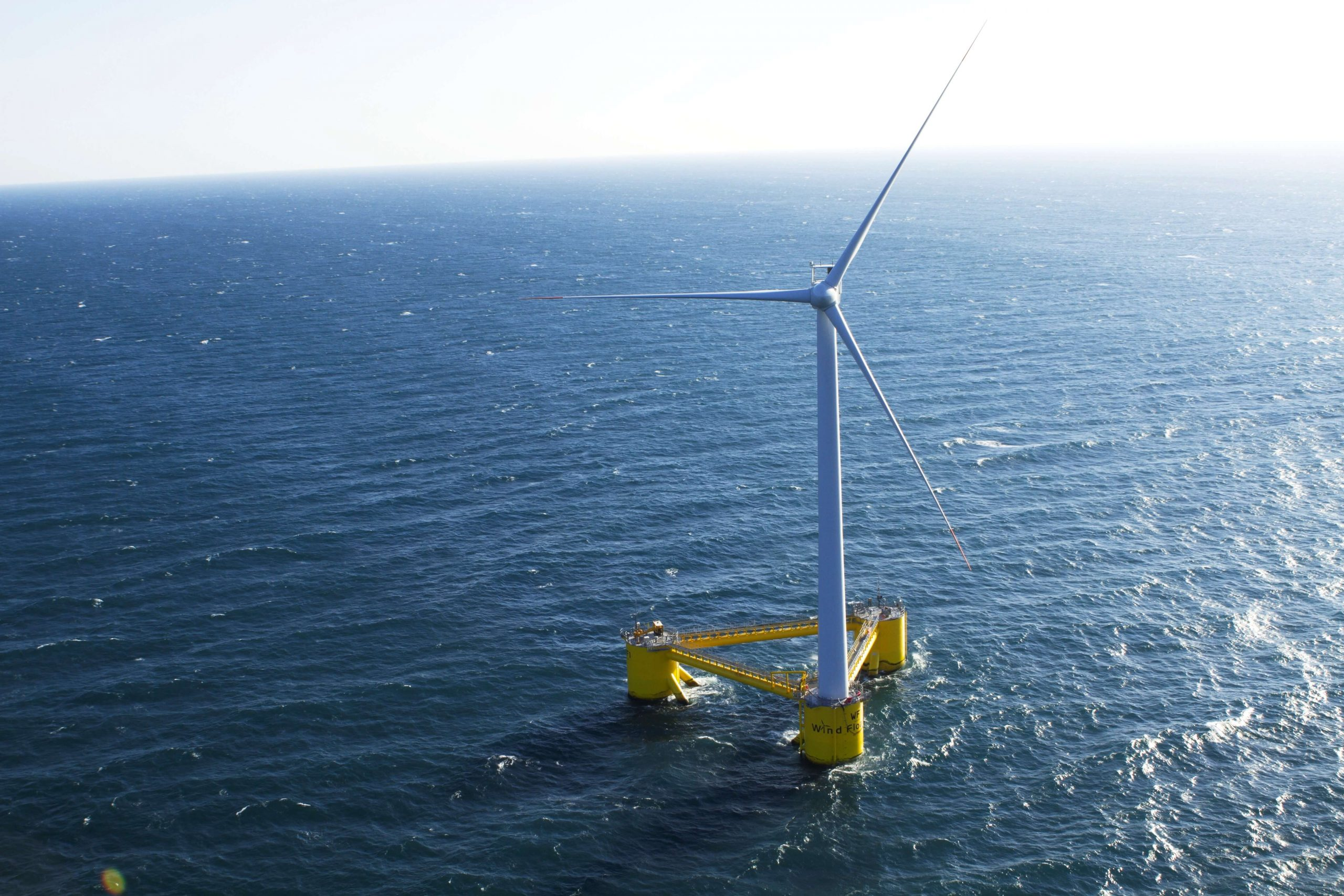 a single floating wind turbine with a yellow platform